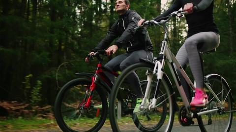 Steadicam shot of mountain biking couple riding on bike trail at sunset doing Footage