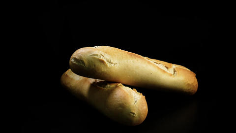 Freshly baked bread rotates against black background Footage