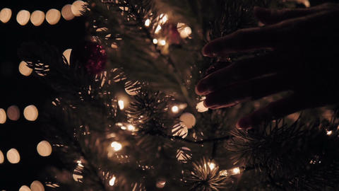 Hand woman touching Christmas ball on tree with bokeh lights in Christmas time Footage
