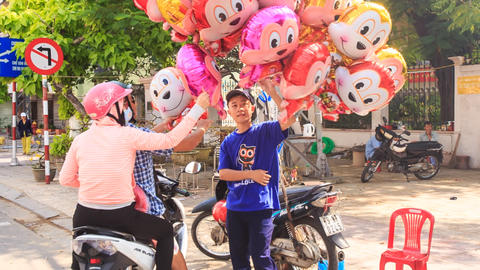 Guy Sells Funny Balloons to Couple on Scooter in Vietnam Footage