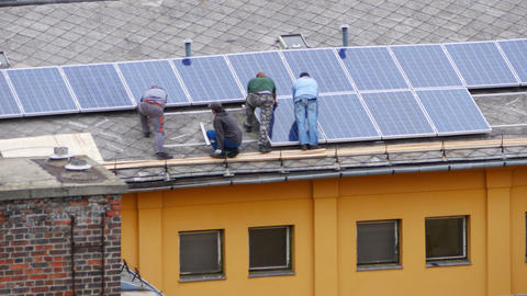 worker installing solar panel roof top apartment Live Action