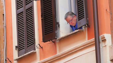 ROME - ITALY, AUGUST 2015: italian woman looking from window Footage