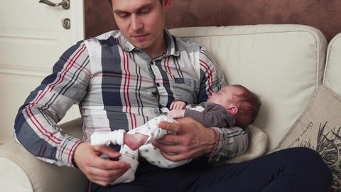 father putting on a sock to his newborn baby Footage