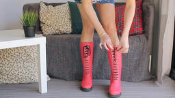 The young beautiful woman clothes and laces red boots Footage