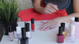 Woman makes manicure, paint her nails with red color ビデオ