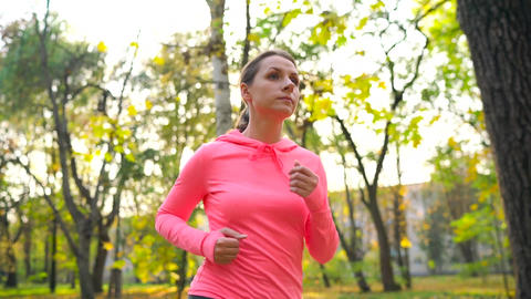 Close up of woman running through an autumn park at sunset. Slow motion Live Action