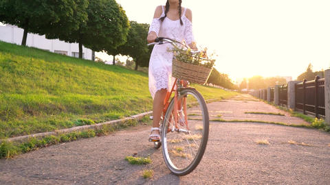 Young beautiful woman standing near her bicycle at sunset. Slow motion Footage