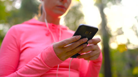Woman with headphones and a smartphone chooses the music for a run through the Footage