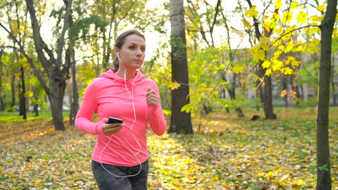 Close up of woman with headphones and smartphone running through an autumn park Live Action