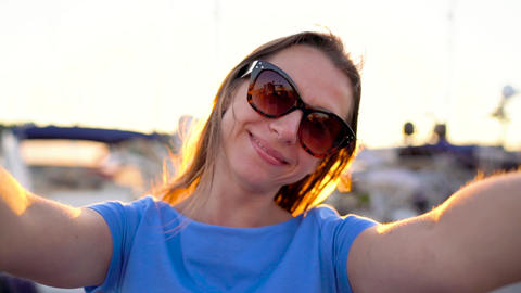 Woman in sunglasses makes selfie on the background of the marina with a lot of Live Action