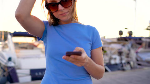 Woman in sunglasses talking on the smartphone while walking down a dock with a Footage