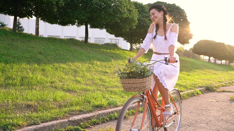 Young beautiful woman riding a bicycle at sunset Live Action