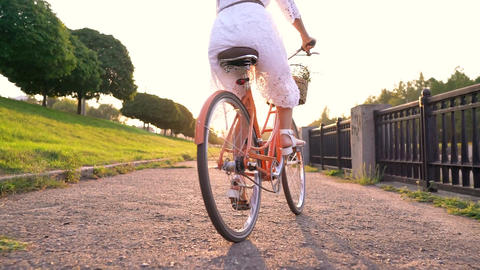Young beautiful woman standing near her bicycle at sunset. Slow motion Live Action