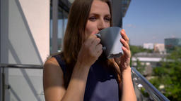 Woman relaxing on balcony holding cup, drinking coffee Footage