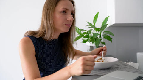 Attractive woman using her laptop while having a breakfast Footage