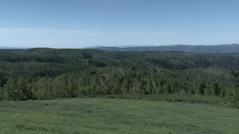 View across the tops of the rocky mountains panning right Footage