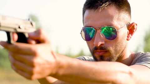 Young man with a gun is aiming to shoot a close up Footage