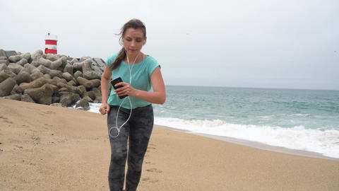 Athletic woman running along the beach. Slow motion Footage
