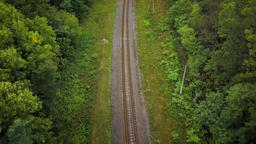 Flight over a railway surrounded by forest Footage