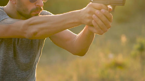 Young man is shooting from a gun, close up. Shooting exercise Footage