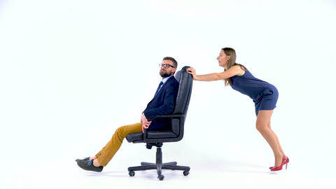 Girl pushing her co worker on a swivel chair in studio silly time Footage
