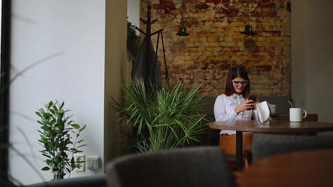 Smartphone girl using app on phone drinking coffee smiling in cafe. Beautiful Footage