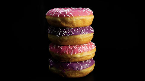 Tasty donut in close-up rotating against black background Footage