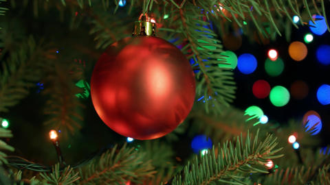 Christmas tree ball on background of blurred fairy lights garland Footage