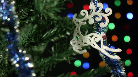 Christmas toy reindeer on the Christmas tree, festive decoration lights Footage