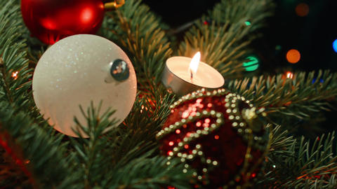 Christmas tree with balls, candles and garland on a dark background Footage