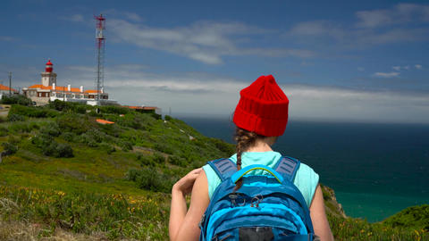 Woman with a backpack goes on a picturesque hilly terrain to the lighthouse near Footage