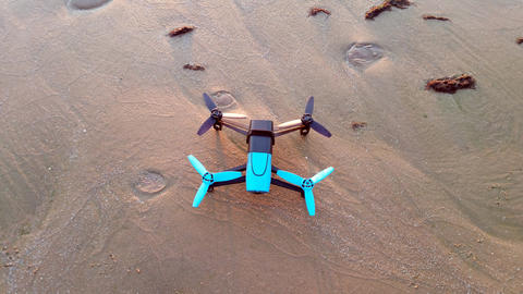 black and blue drone standing on the sand, view from above Foto