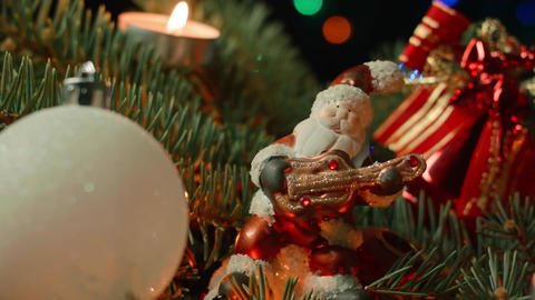 toy Santa on the Christmas tree with Christmas balls and candle Footage
