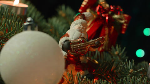 Christmas balls in front of a light background, a toy Santa with lights Footage