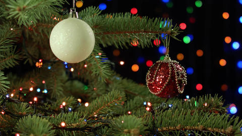 decorated Christmas tree red and white orbs on a dark background with garland Footage