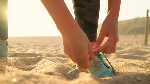 Running shoes - woman tying shoe laces on sandy beach at sunset. Slow motion Footage