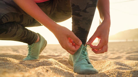Running shoes - woman tying shoe laces on sandy beach at sunset Footage