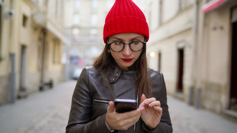 Woman with red lips uses smartphone and strolls along the medieval street Footage