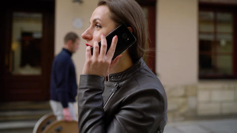 Woman with red lips talking on the smartphone and strolls along the medieval Footage