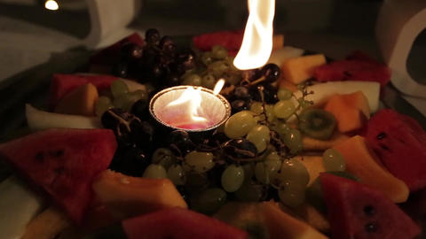 Wedding decorations, a candle lit among fruits Footage