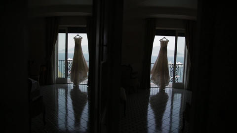 Wedding dress hanging in doorway, background see Archivo