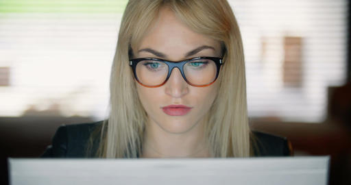 Serious young woman using computer late at work Footage