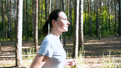 girl running among the trees, watches over the health, fitness training Footage