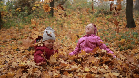 Two happy kids throwing fallen leaves up in fall Footage