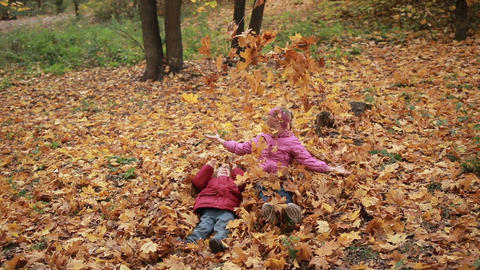 Carefree kids playing in a pile of fall leaves Footage