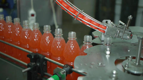 production line conveyor screw cap on a bottle of lemonade soda mineral water Archivo