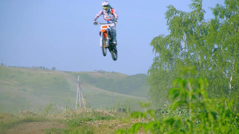 Racer jumping in to camera on motocross track aerial shot. Wide shot of in front Live Action