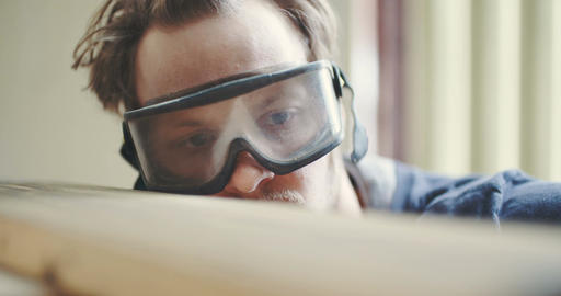 Carpenter In Protective Glasses checking wooden board Footage