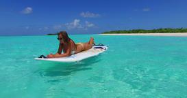 v11944 one 1 beautiful young girl in bikini sunbathing on surfboard paddleboard Footage