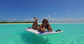 v11953 one 1 beautiful young girl in bikini sunbathing on surfboard paddleboard Footage
